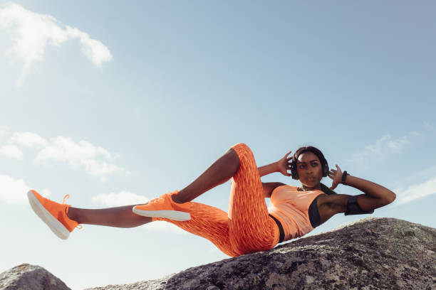fit woman stretching at the beach - sit ups stock photos and pictures