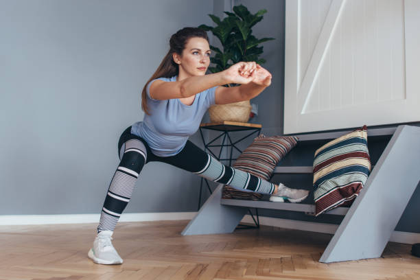 Fit woman stretching legs Lateral Lunge exercise. Fit woman stretching legs Lateral Lunge exercise lateral surface stock pictures, royalty-free photos & images