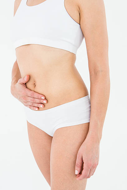 Fit woman suffering from stomach pain stock photo
