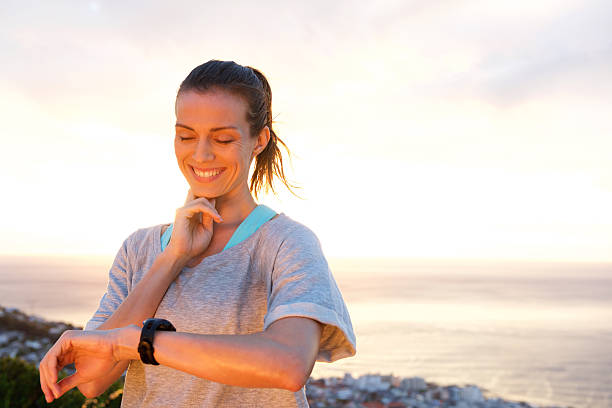 Fit woman timing her heart rate with watch stock photo