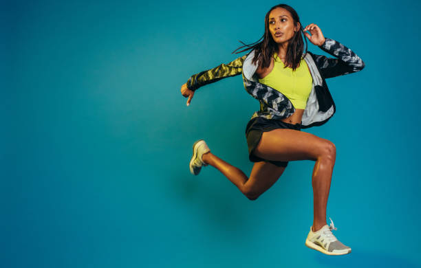 Fit woman training in studio Full length of fit young woman running. Female runner sprinting on blue background with copy space. women's track stock pictures, royalty-free photos & images