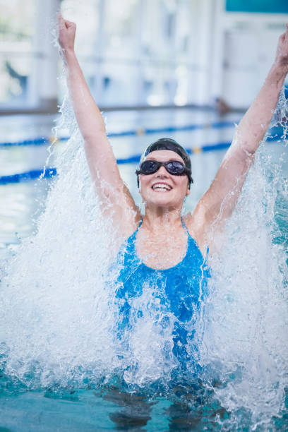 Fit woman triumphing with raised arms stock photo