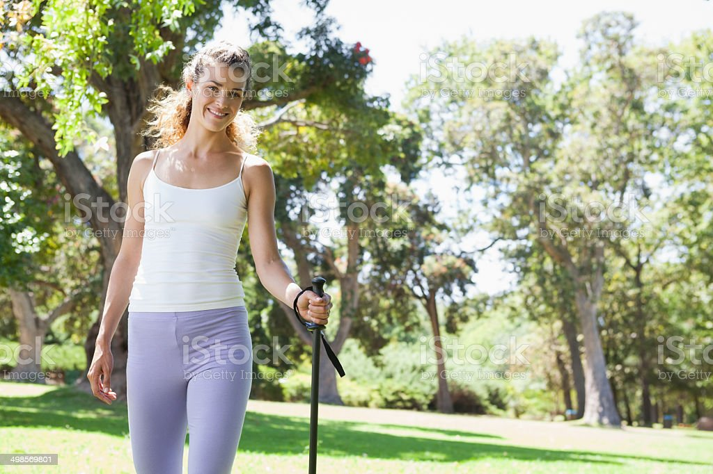 Fit woman walking with a hiking pole through the countryside royalty-free stock photo