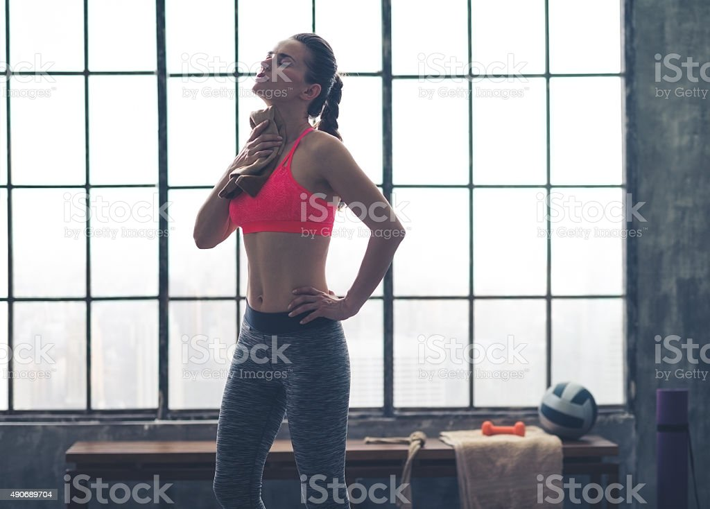 Fit woman wiping sweat off neck in loft gym stock photo