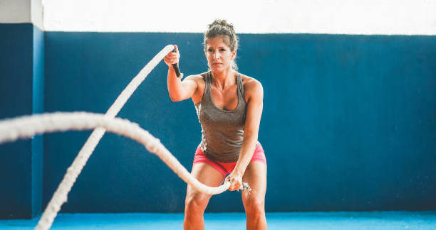 Fit woman with battle rope in functional training fitness gym - Female athlete doing workout session inside wellness club center - Body building and sport trends concept - Focus on her body stock photo