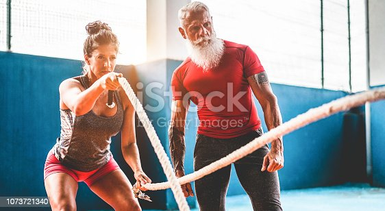 istock Fit woman with battle rope in functional training fitness gym - Tattooed personal trainer motivating female athlete inside wellness club center - Workout and sport trends concept - Focus on man face 1073721340