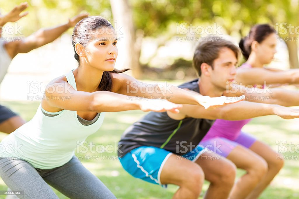 Fit Woman With Friends Practicing Squat Exercise In Bootcamp stock photo