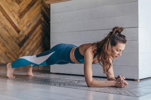 fit kobieta pracuje na mięśnie brzucha robi ćwiczenia deski, podstawowy trening w domu. - deska zdjęcia i obrazy z banku zdjęć
