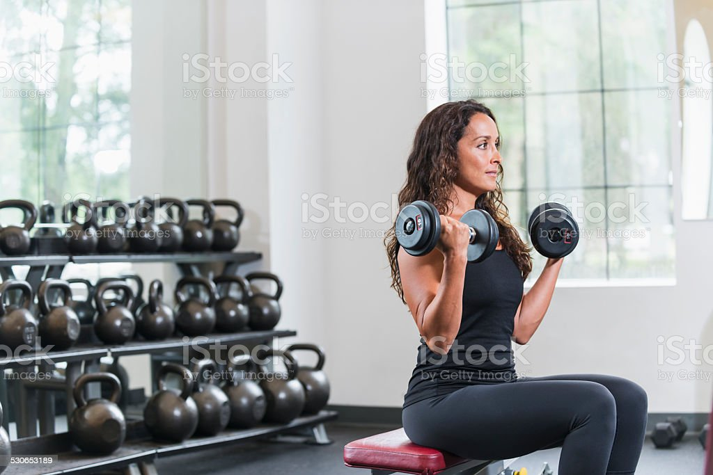 Fit woman working out at the gym lifting dumbbells stock photo