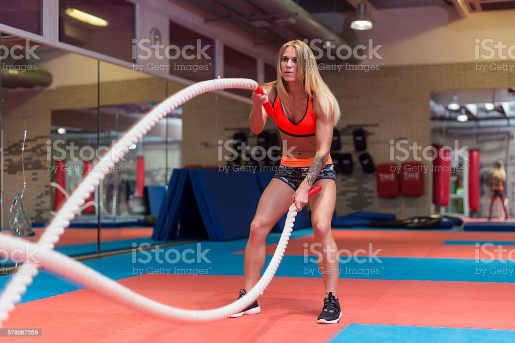 Fit woman working out with battle ropes at a gym. stock photo