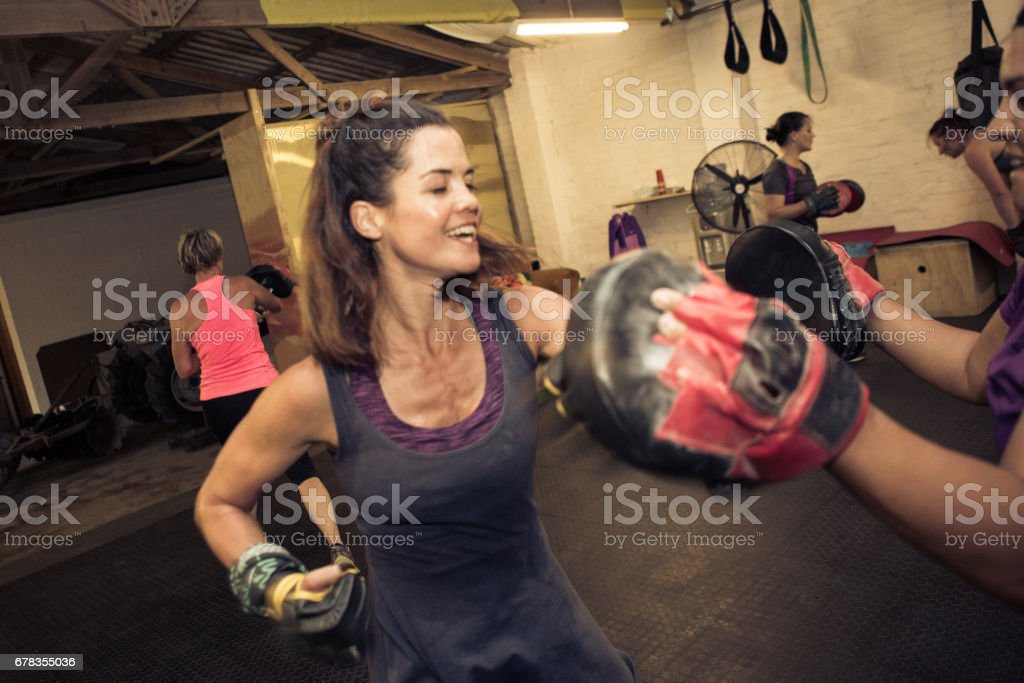 Fit women punching with her fitness trainer stock photo