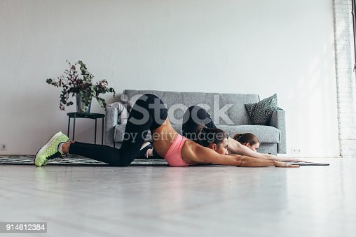 istock Fit women working-out at home performing backbend 914612384