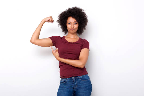 fit young african woman pointing at arm muscles on white background Portrait of fit young african woman pointing at arm muscles on white background flexing muscles stock pictures, royalty-free photos & images
