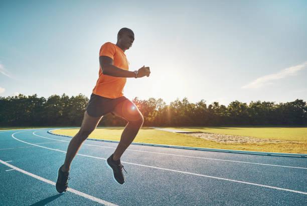 forma joven atleta corriendo solo por una pista de atletismo - vuelta completa fotografías e imágenes de stock