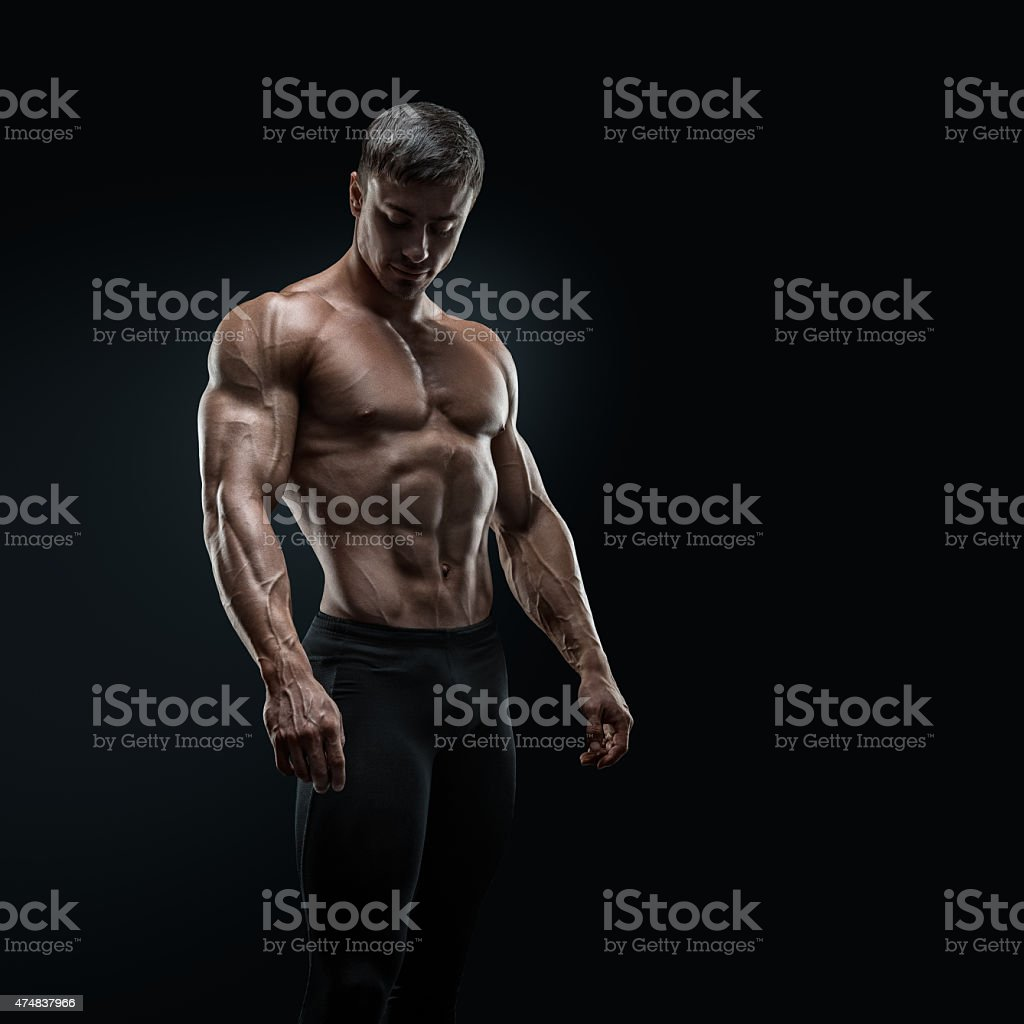 Fit young bodybuilder posing over black background foto