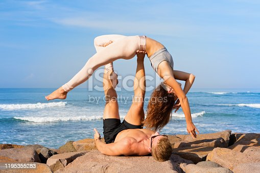 816941230 istock photo Fit young couple doing acro yoga exercise at sea beach 1195355283