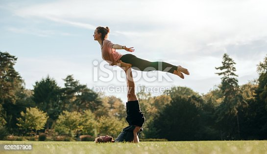 istock Fit young couple doing acro yoga on park 626267908