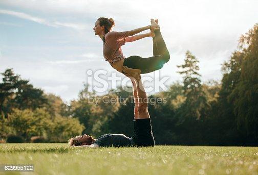 istock Fit young couple doing acro yoga 629955122