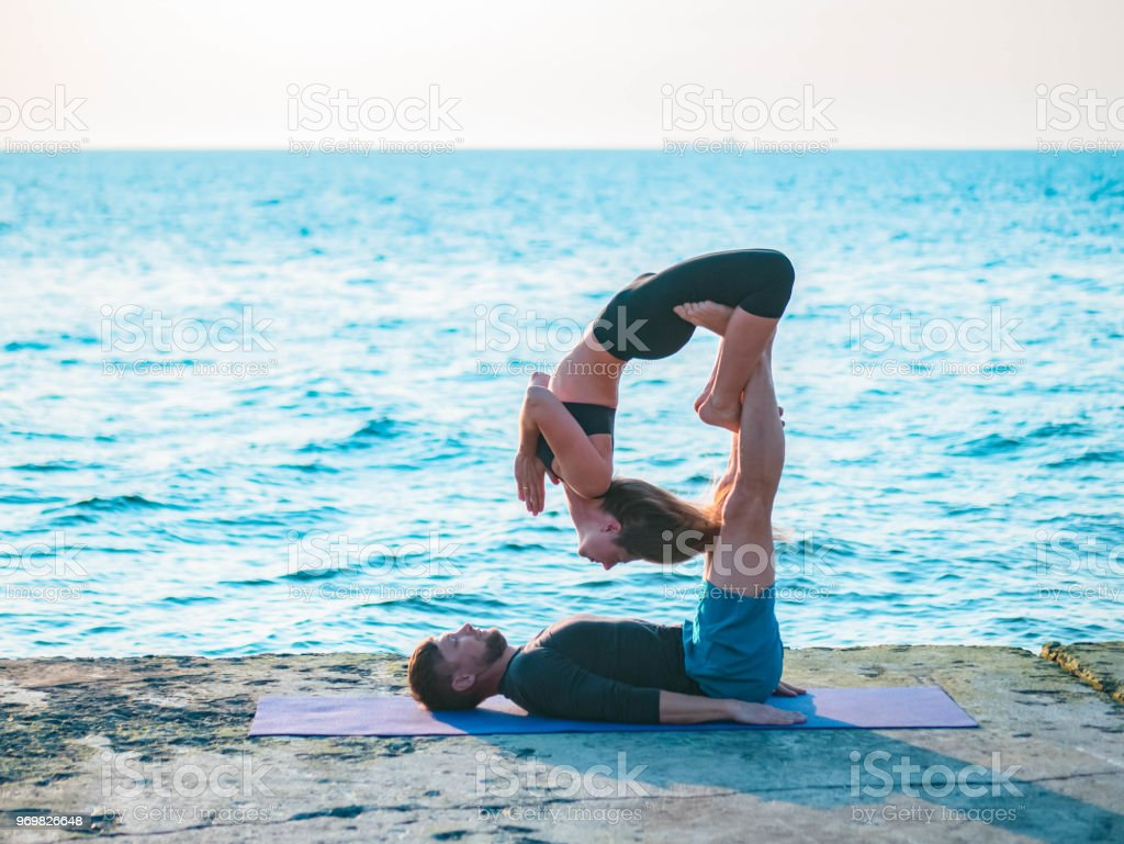 Fit young couple doing acro-yoga at sea beach. Man lying on concrete plates and balancing woman on his feet. Beautiful pair practicing yoga together stock photo