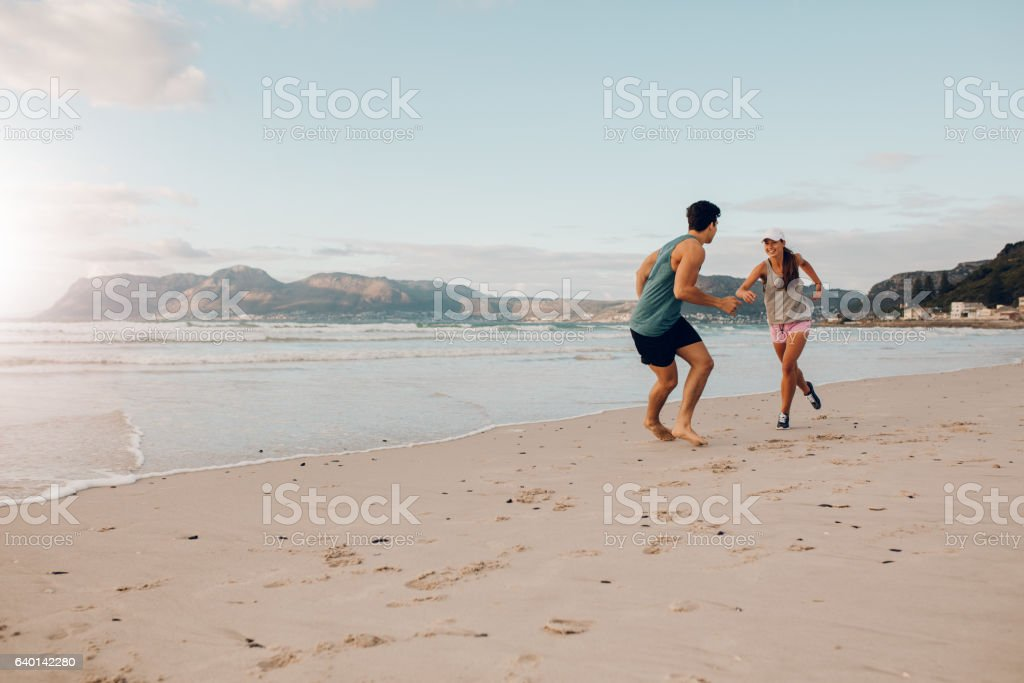 Fit young couple playing on the beach stock photo