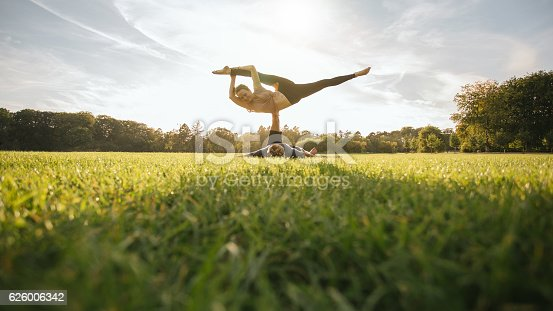 istock Fit young couple practising acroyoga 626006342