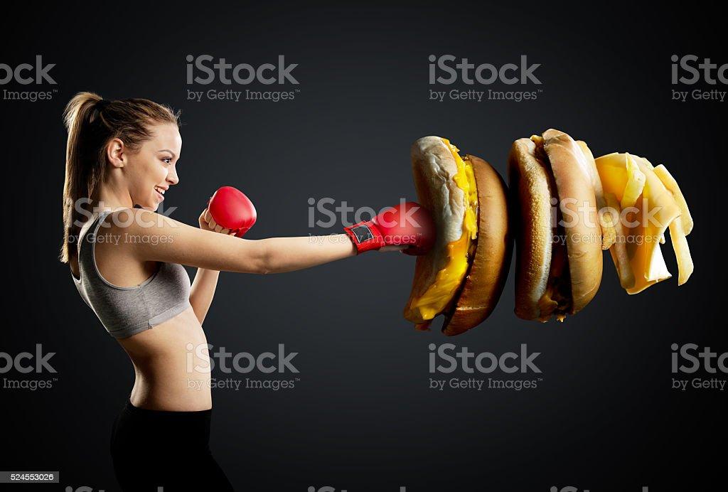 Passen, junge, dynamische Frau Boxen ungesund Essen, Schwarzer Hintergrund – Foto