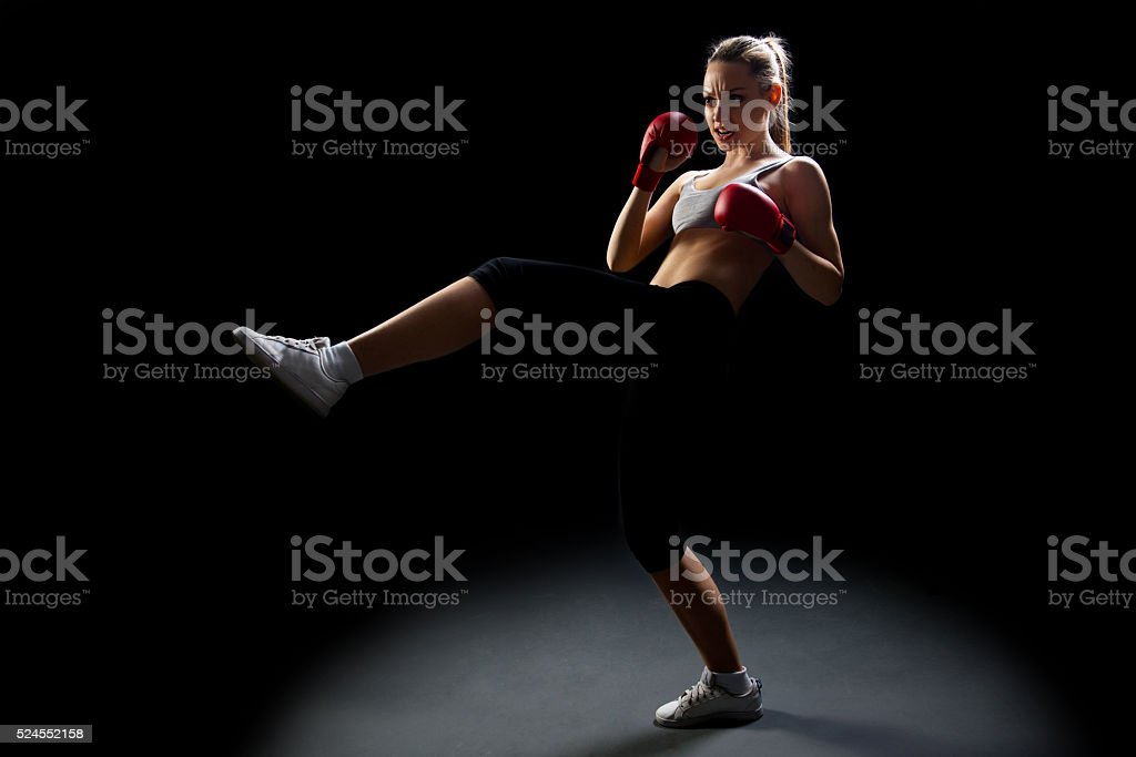 Fit, young, energetic woman kickboxing, black background stock photo