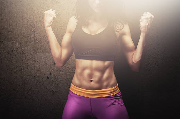 Fit young female fitness model posing and showing her muscles stock photo