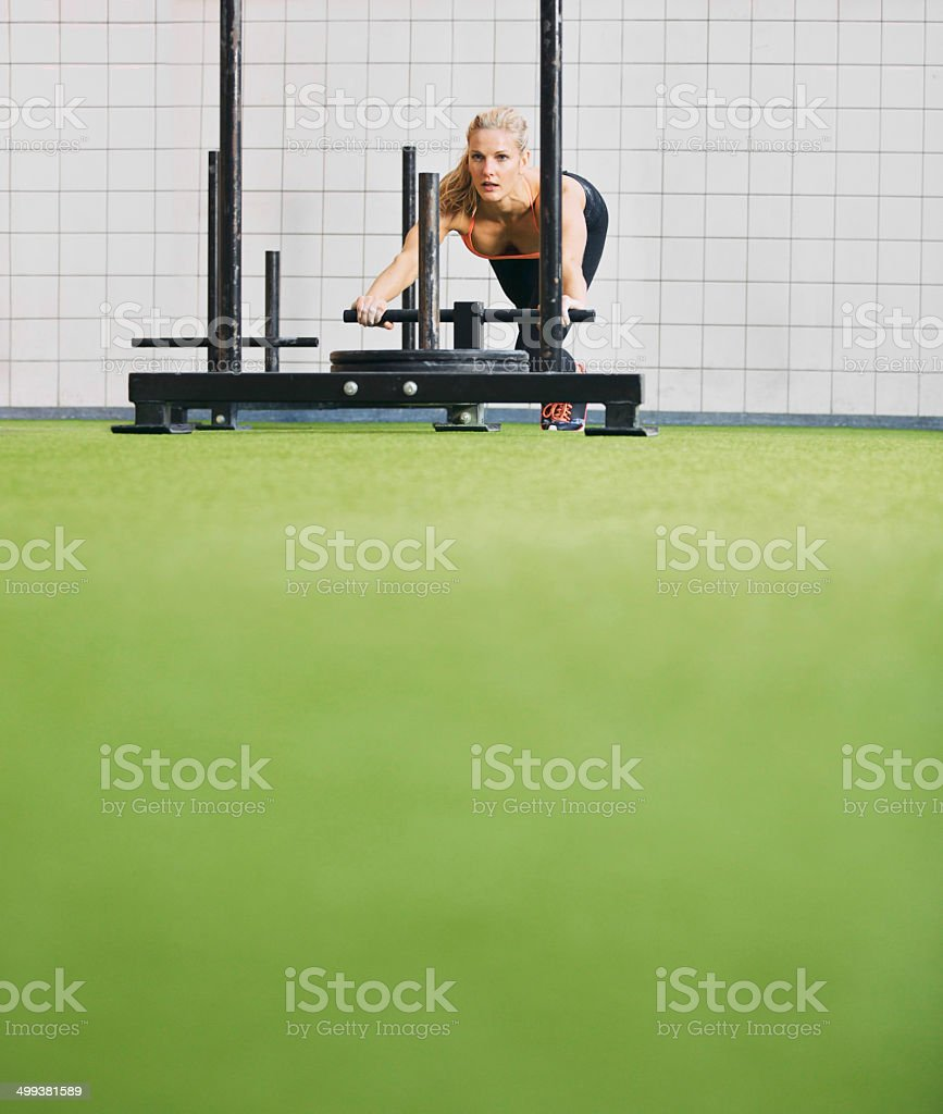Fit young female using prowler exercise equipment at gym stock photo