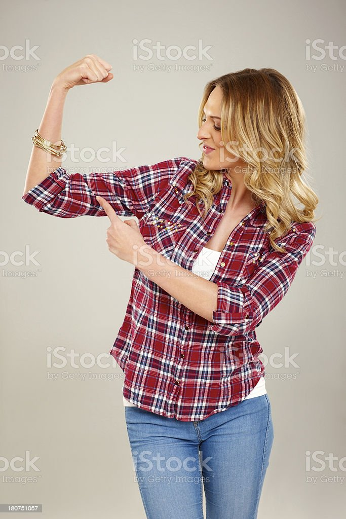 Fit young lady flexing her biceps against grey royalty-free stock photo