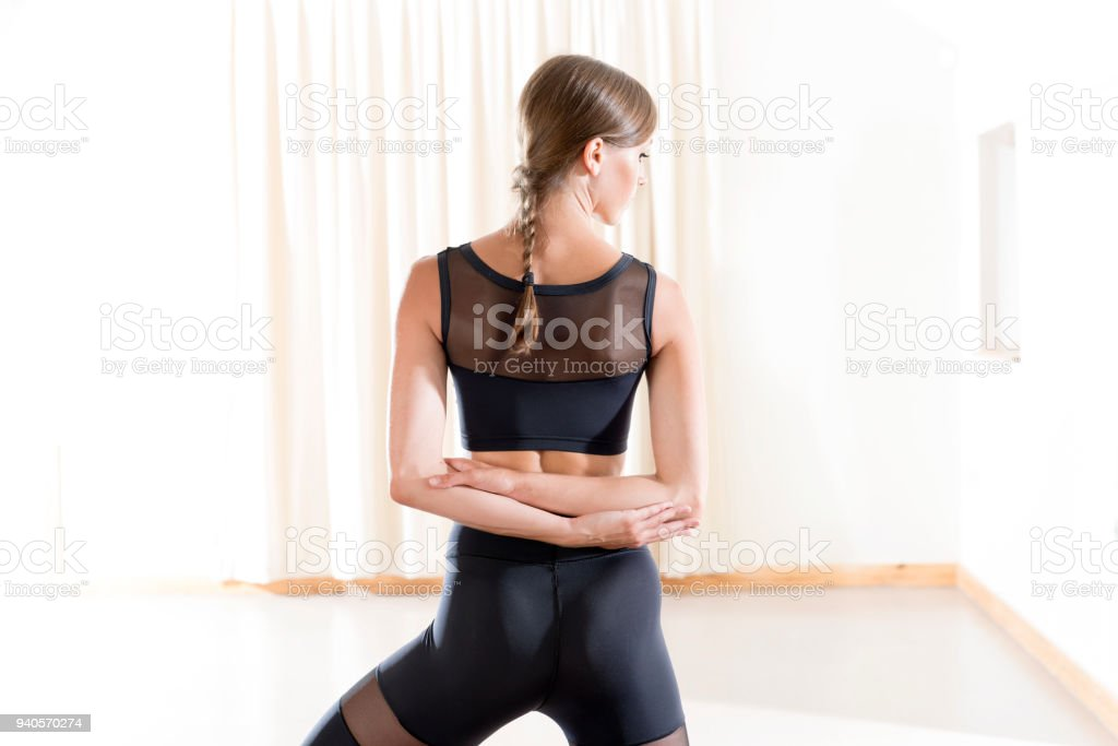 Fit Young Lady Performing a Standing Reversed Arm Shoulder Stretch stock photo