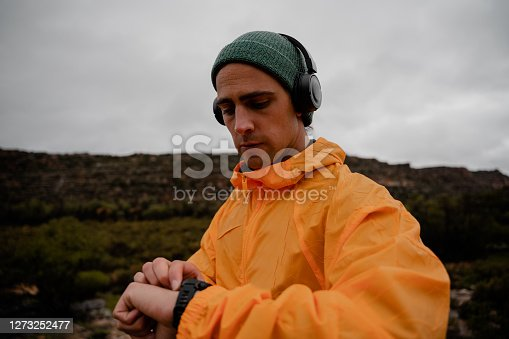 Fit young caucasian male athlete setting up smartwatch to track heart rate activity listening to music in headphones from smartphone on run on wet gravel mountain path with lush bushes and cloudy weather. High quality photo