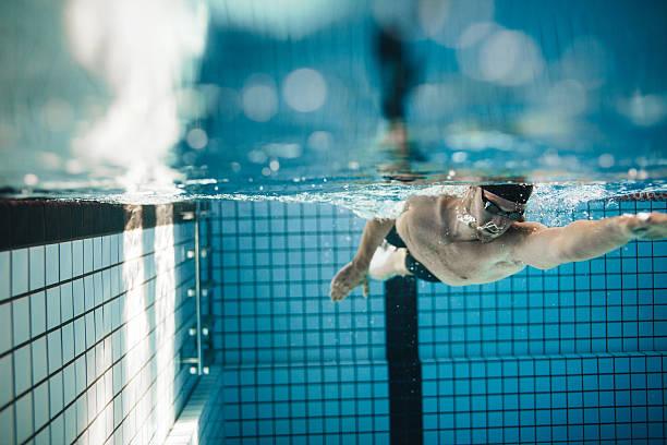 fit young male swimmer training in the pool - vuelta completa fotografías e imágenes de stock