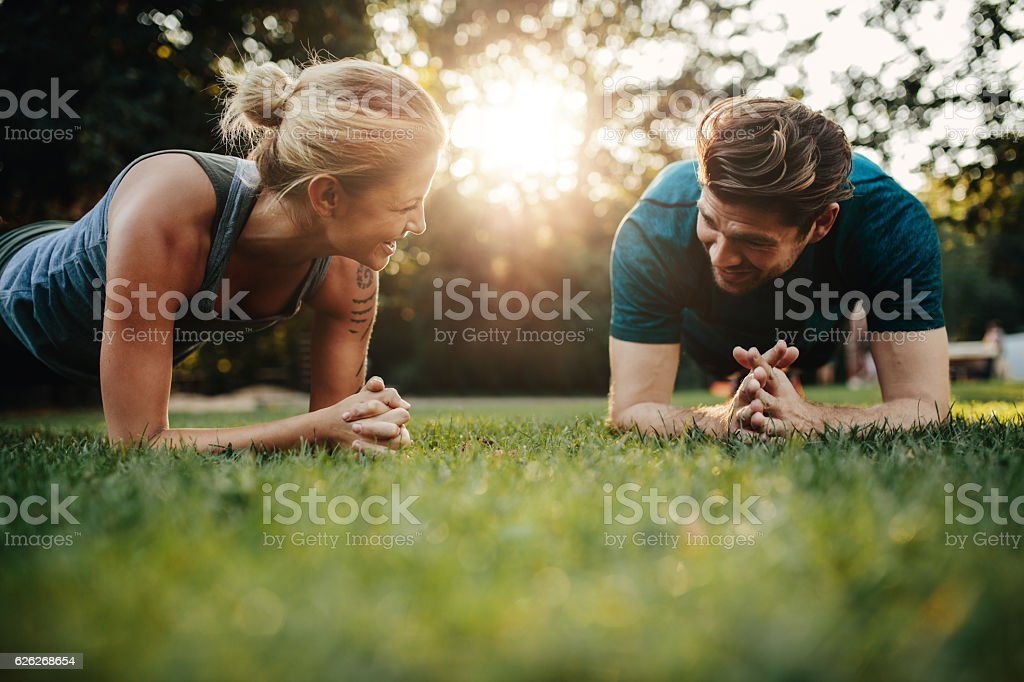 Fit young man and woman exercising in park stock photo