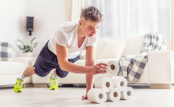Fit young man creatively using excess toilet paper rolls for home plank and pushups workout in the living room. stock photo