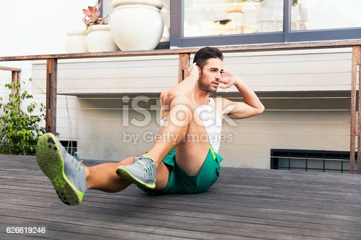 Full length of fit young man doing crunches. Determined male is exercising on floorboard. He is wearing sportswear in backyard.