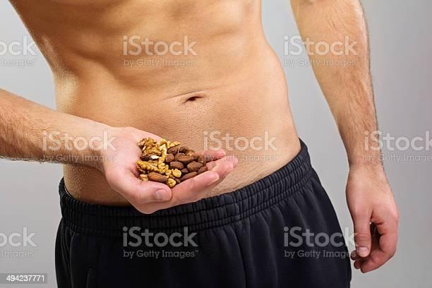 Fit Young Man Holding Tuercas Sanos Foto de stock y más banco de imágenes de Fruto seco