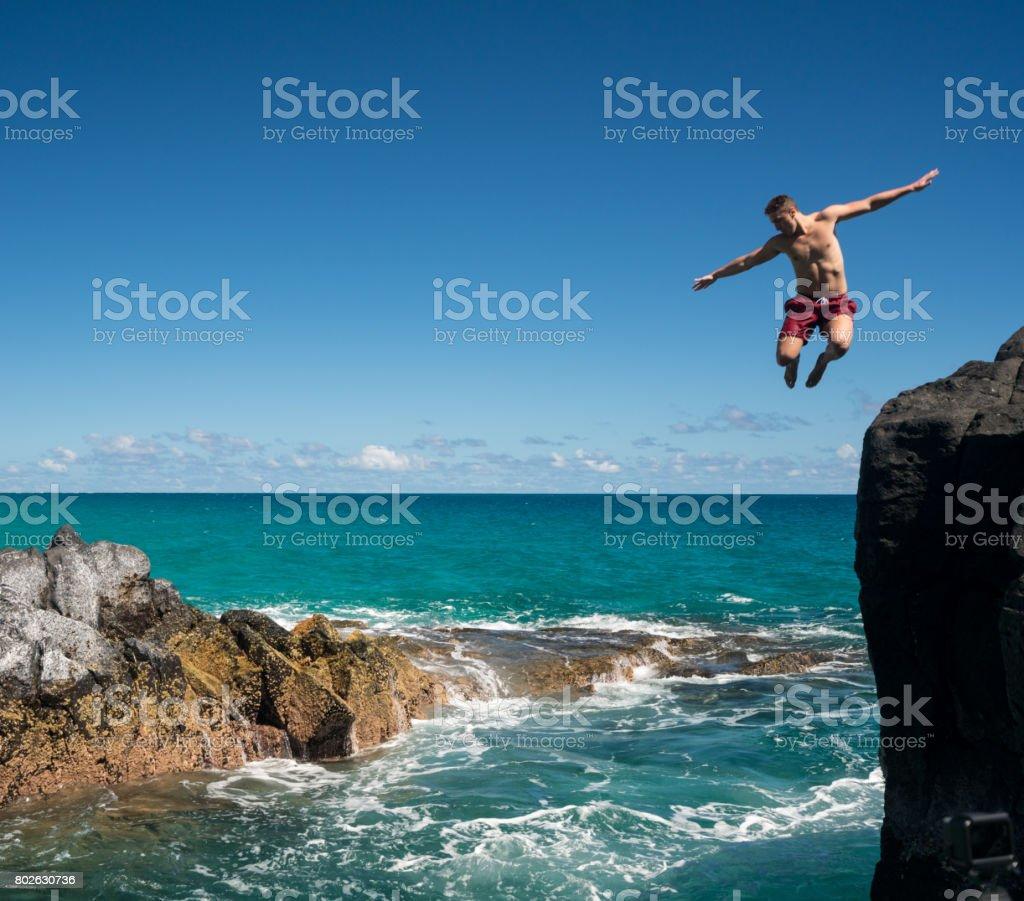 Fit young man jumps into ocean at Lumahai beach Kauai stock photo