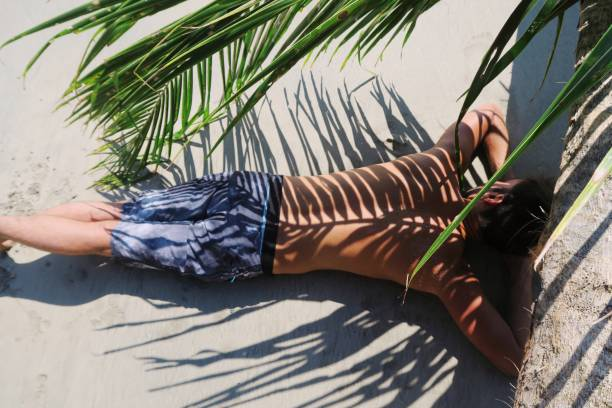 Fit young man laying / standing under the palm leaf / palm leaf shade stock photo