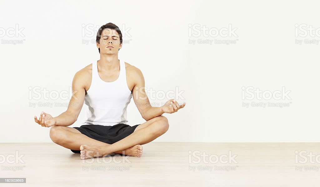 Fit young man meditating in lotus position royalty-free stock photo