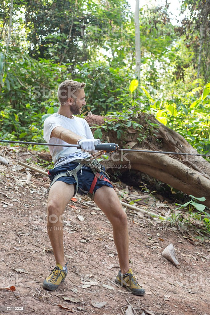Fit young man on zip-line ready to depart stock photo
