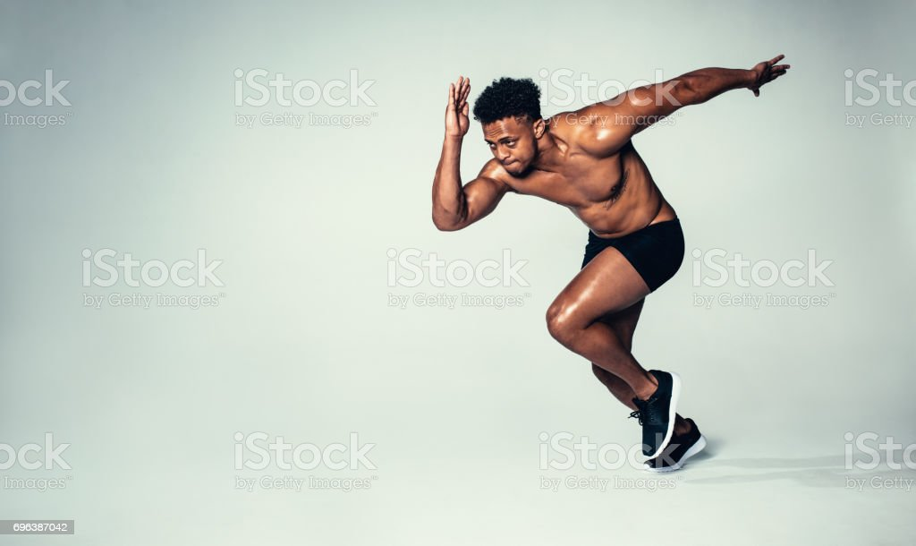 Fit young man running over grey background stock photo