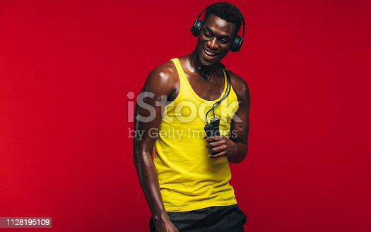 Fit young man listening to music on headphones with a skipping rope in hand on red background. Fit young man taking after from workout.
