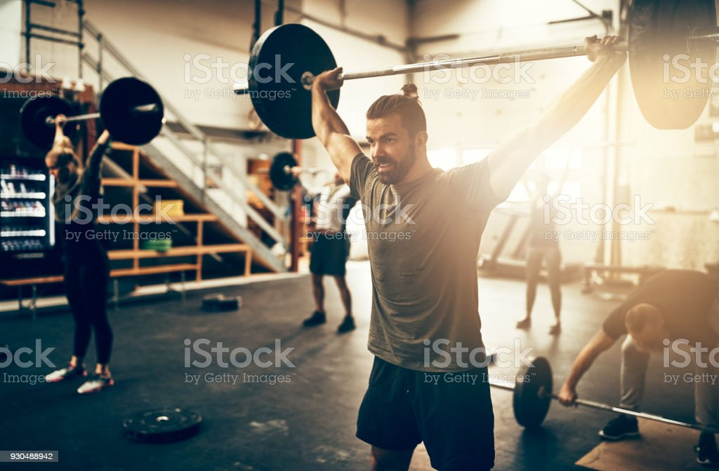 Fit young man weight training in a gym class stock photo