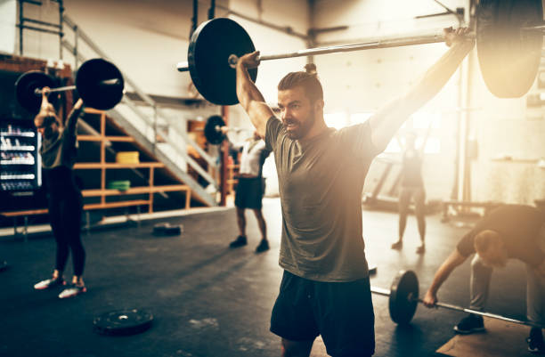 fit young man weight training in a gym class - pesistica foto e immagini stock