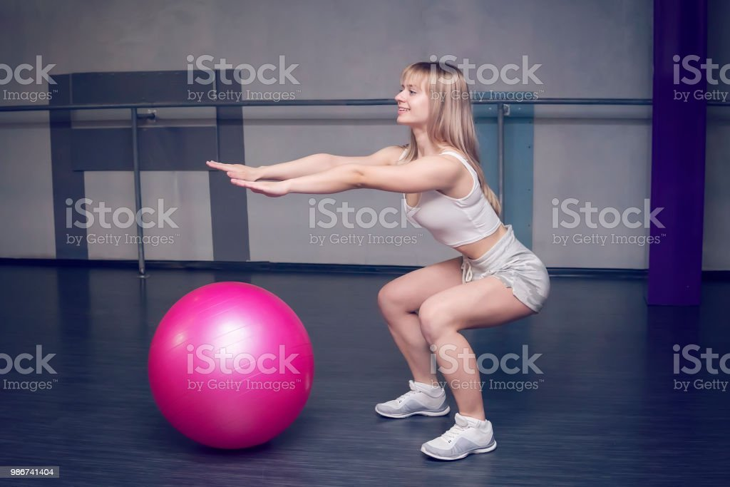 Fit young pretty woman doing squats exercises with fitness ball. side view. stock photo