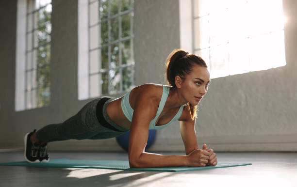 fit young woman doing push ups at gym - push up stock photos and pictures