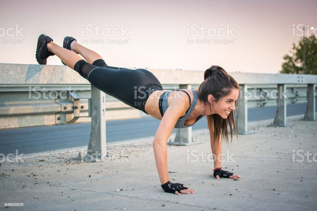 Fit young woman doing push ups over bridge's fence during evening training outdoors. stock photo