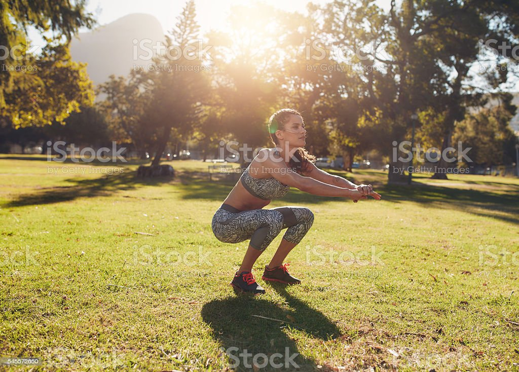 Fit young woman doing squatting in park stock photo