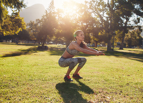 Fit young woman doing squatting in park - foto de acervo
